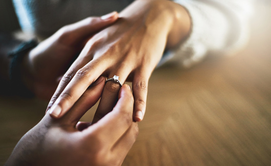 Cropped shot of a man putting an engagement ring onto his girlfriend's finger