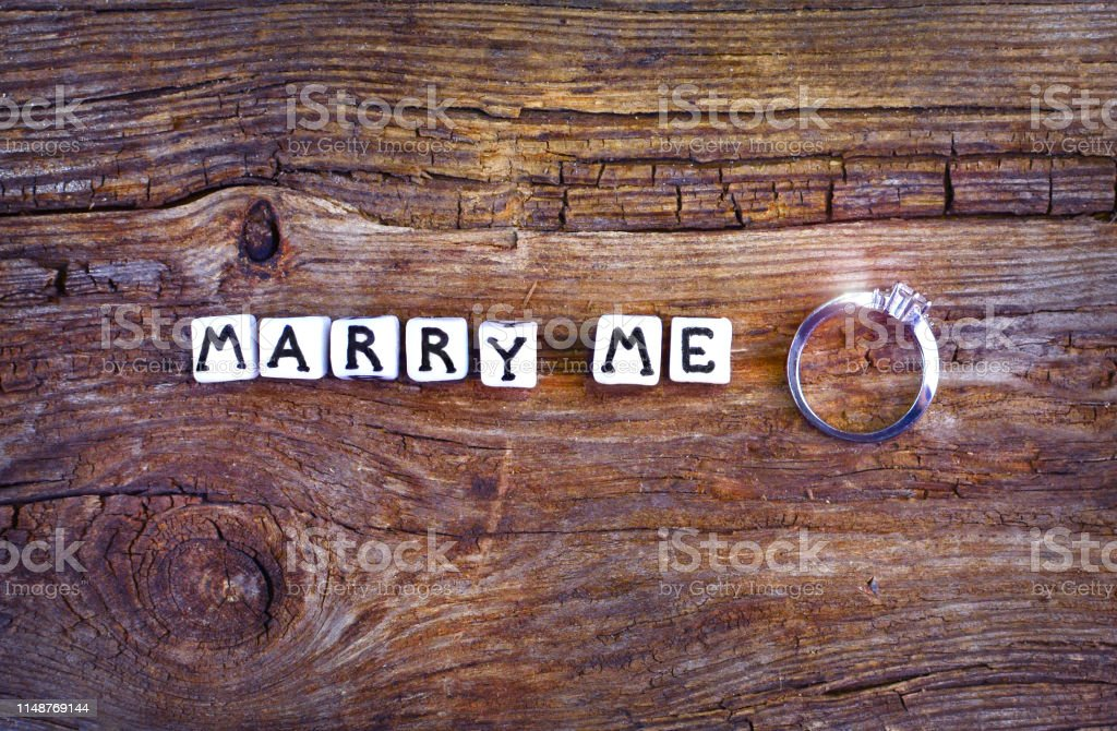 Will you marry me? An offer of marriage on rustic background. Wording...