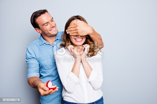 1129577106 istock photo Will you marry me? Handsome man with bristle in jeans shirt making unexpected surprise for his beautiful, charming, joyful lover in casual outfit, closing her eyes with hands over grey background 926598076