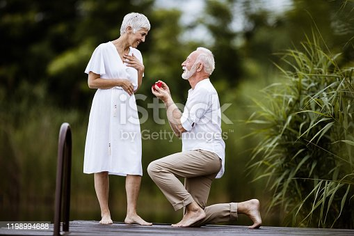 Romantic senior man proposing to his girlfriend on a pier.