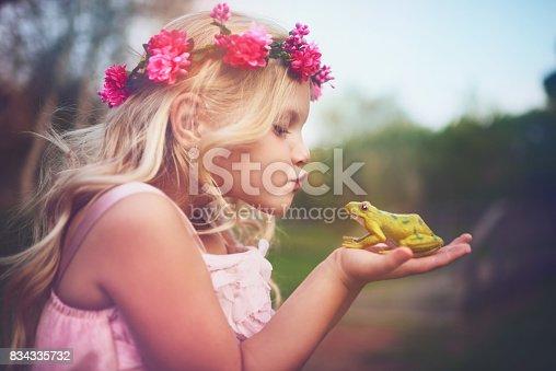Shot of a cheerful little girl holding a frog and going in for a kiss while standing outside in nature