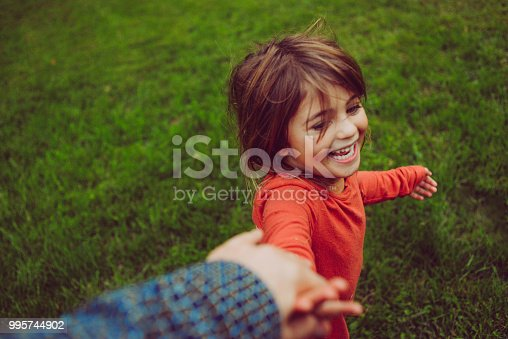Adorable, rambunctious little age, age 4, runs in the grass, full of laughter, innocence and joy. She holds the hand of an adult that is out of frame. She is joyful and the grass is lush and green