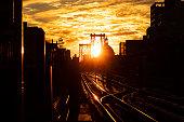 Sunset over the Williamsburg Bridge and subway tracks in Brooklyn, New York City.