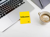 istock Willkommen or welcome with smiley face icon on desk 923609172