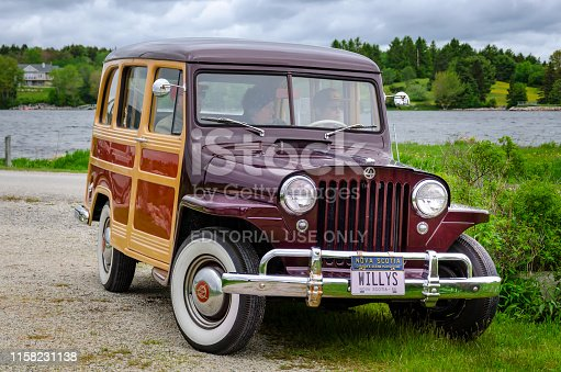 Chester, Nova Scotia, Canada - June 22, 2019 : 1950 Willys Jeep Woodie Station Wagon at annual Graves Island Car Show at Graves Island Provincial Park, Chester, Nova Scotia, Canada. Three people sit inside the classic Jeep.