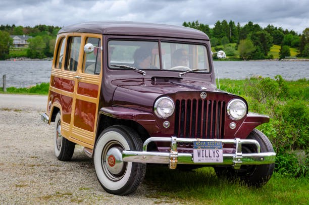 1950 Willys Jeep Woodie Station Wagon Chester, Nova Scotia, Canada - June 22, 2019 : 1950 Willys Jeep Woodie Station Wagon at annual Graves Island Car Show at Graves Island Provincial Park, Chester, Nova Scotia, Canada. Three people sit inside the classic Jeep. willys stock pictures, royalty-free photos & images