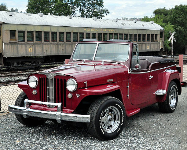 Willys Jeepster parked by a vintage rail car Jamestown, California, United States - June 25, 2013: A red 1948 Willys Jeepster convertible parked near a vintage railroad car at the train station  in Jamestown, California willys stock pictures, royalty-free photos & images