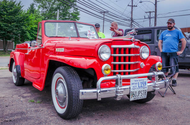 1950 Willys Jeepster - the original SUV Truro, Nova Scotia, Canada - July 14, 2019 : Two older men chat near the classic Jeep while another younger man gives it a good look over. willys stock pictures, royalty-free photos & images