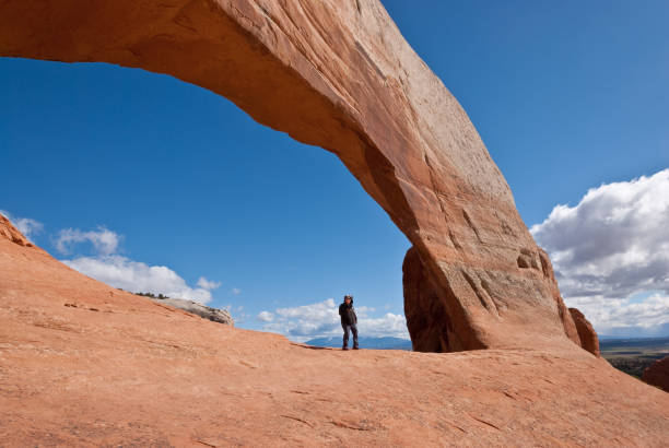 woman standing under wilson arch - jeff goulden stock photos and pictures