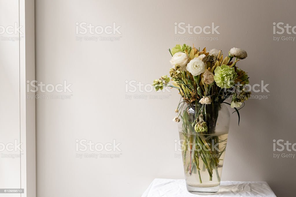 Wilting Flowers In Large Glass Vase Next To Window Stock Photo