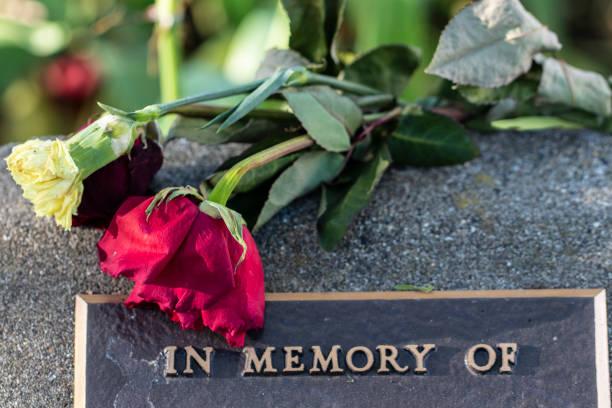 wilting flowers on a memorial - funerale foto e immagini stock