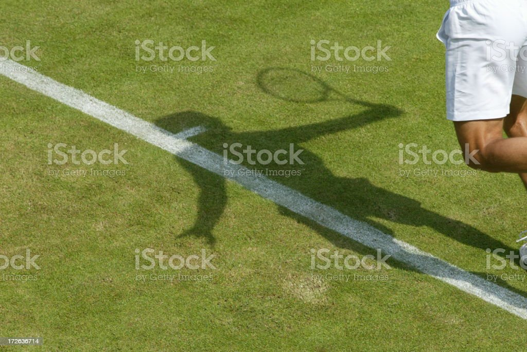 Wimbledon Grass Court Player Serving with shadow stock photo