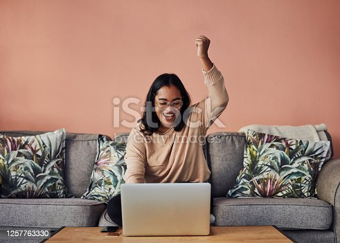 Shot of a young woman cheering while using a laptop on the sofa at home