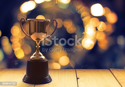 istock Win prize trophy on wood table with background window. 939840782
