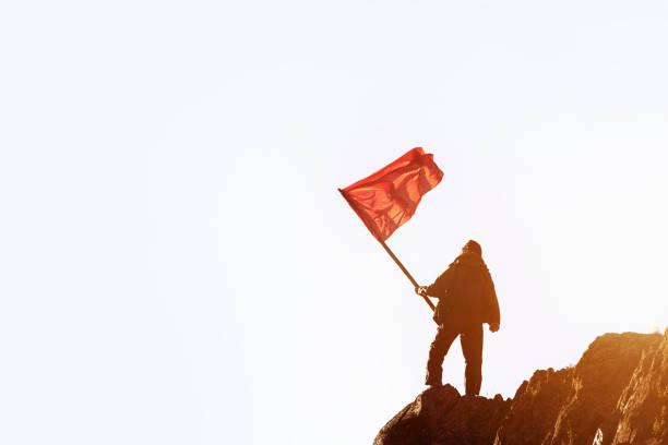 win gewinner konzept mann rote fahne berggipfel - rotes oberteil stock-fotos und bilder