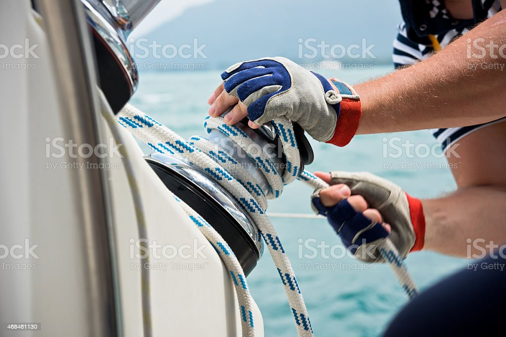 Winch and sailors hands on a sailboat stock photo