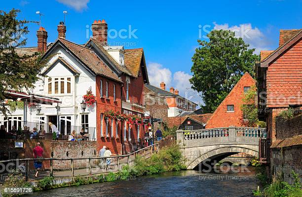 Winchester, UK - September 21, 2014: Riverside path and pub with view along the River Itchen, in Winchester in Hampshire, England. This is close to the city centre and a popular place for tourists and others to walk along.
