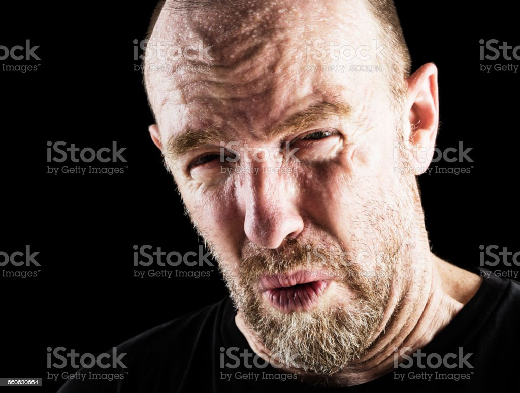 Wincing and grimacing, a mature bearded man against black stock photo