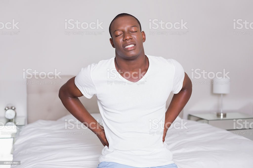 Wincing man sitting on the edge of his bed with stock photo