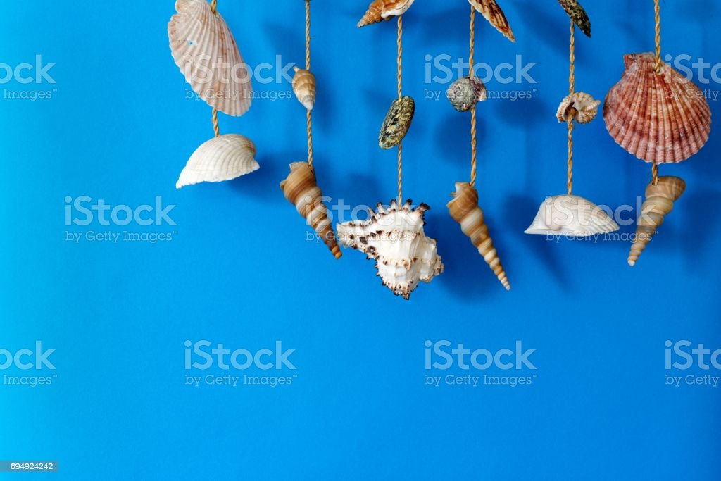 A wind chime with shells on a blue background stock photo