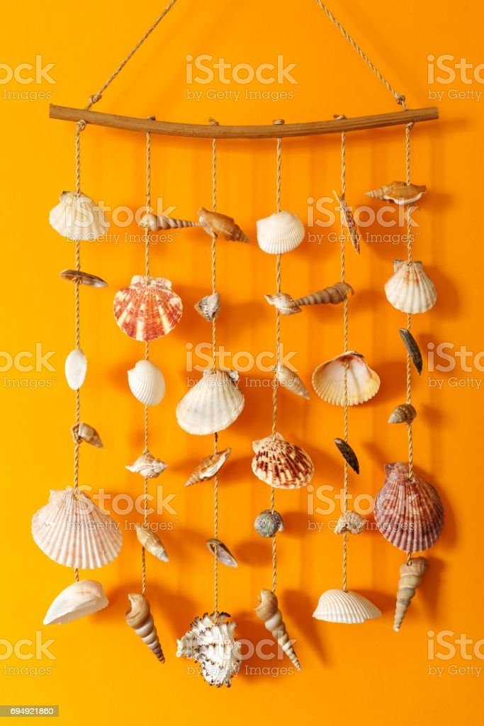 A wind chime with shells on a yellow background stock photo