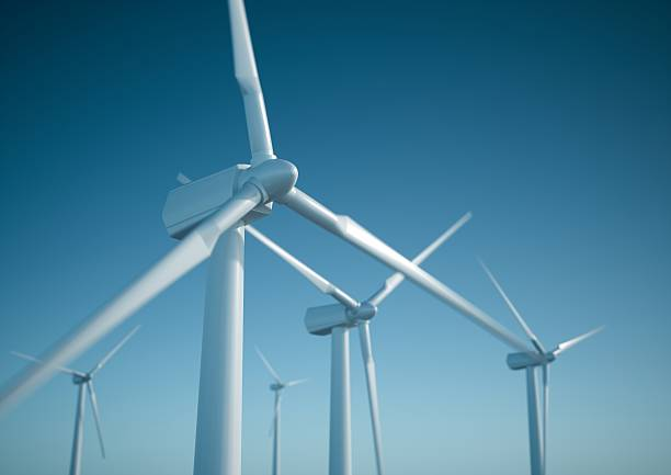 Wind energy turbines White wind turbine generating electricity on blue sky windmill stock pictures, royalty-free photos & images
