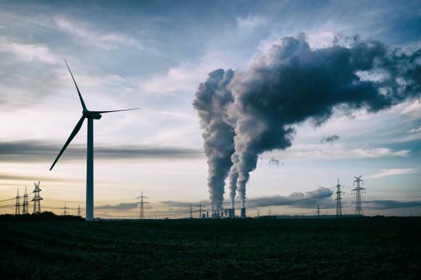 energía eólica frente a central eléctrica de carbón - contaminación ambiental fotografías e imágenes de stock