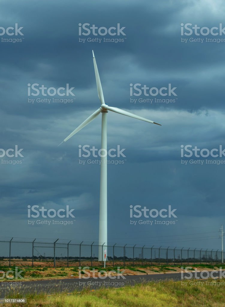 wind energy windmill with weather in distance stock photo