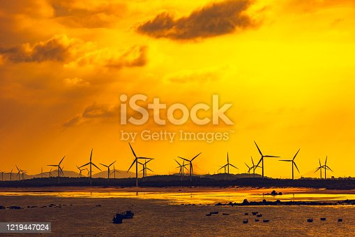 wind farm at beach in sunset.