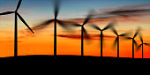wind farm in silhouette at dusk, panoramic frame