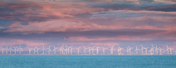 Wind Farm in motion at Sunset in the Solway Firth, United Kingdom stock photo