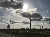 Wind farm with blue sky and dramatic clouds and sunshine