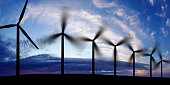 wind farm in silhouette at sunset, panoramic frame