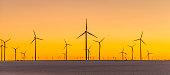 many wind generators in sunset
