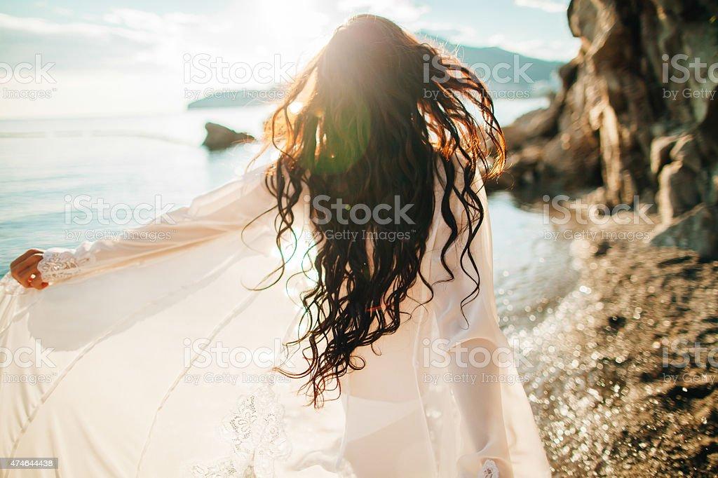 wind im Haar verträumte Mädchen mit sunflare am Strand – Foto