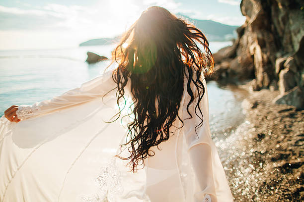 wind in hair dreamy girl with sunflare on beach - beach fashion stock photos and pictures