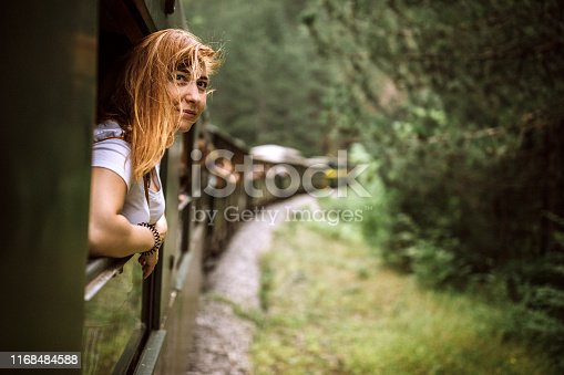 Female tourist traveling in train standing out of window train and looking beautiful nature