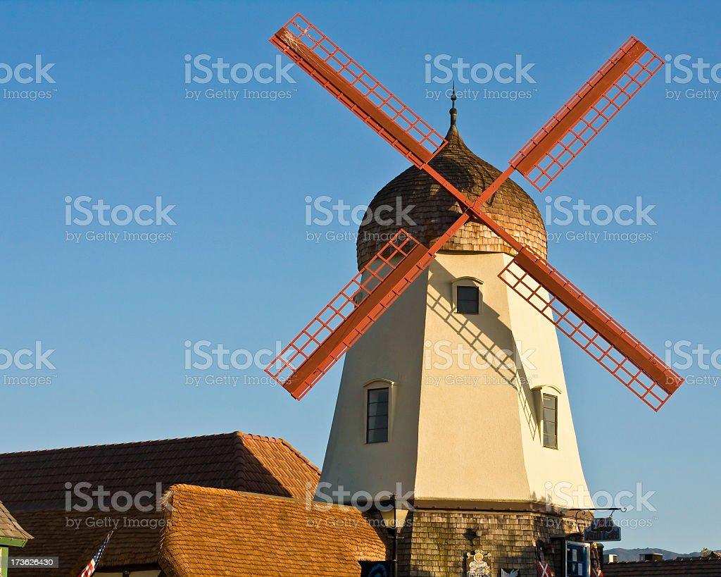 A wind mill with a perfect blue sky background stock photo