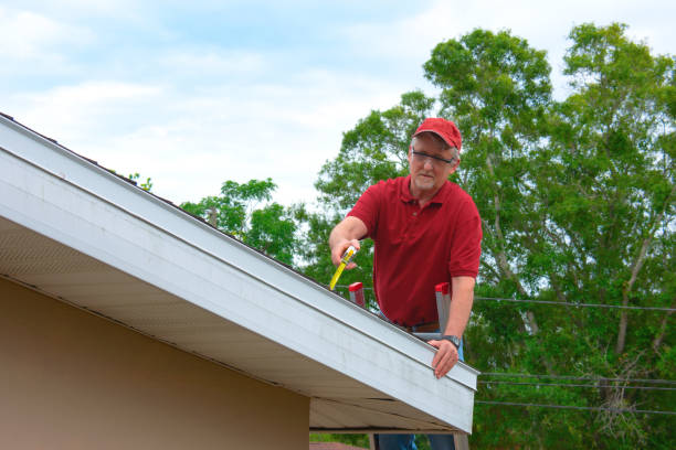 Wind mitigation inspection inspector on a ladder doing inspection on new roof to generate a risk rating stock photo