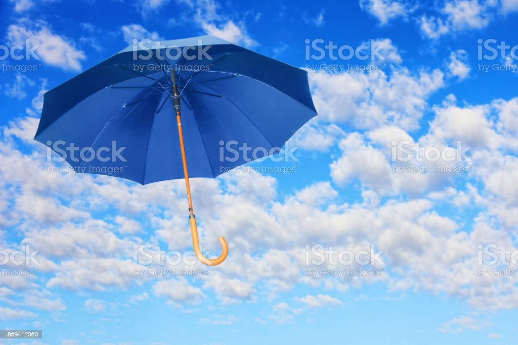 Wind of change concept.Blue umbrella flies in sky against of white clouds. stock photo