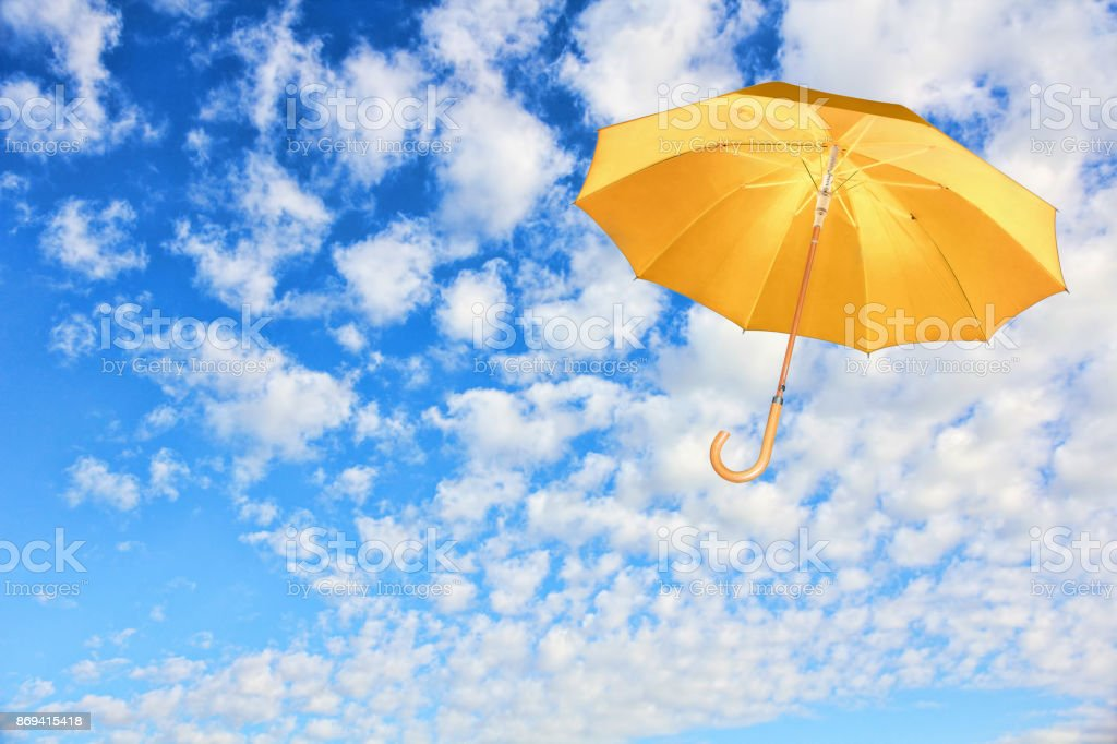 Wind of change concept.Yellow umbrella flies in sky against of white clouds. stock photo