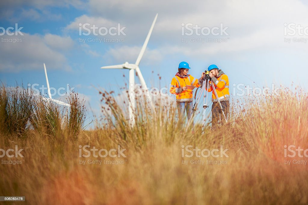 two wind farm engineers using a builder\'s level to plan out the...