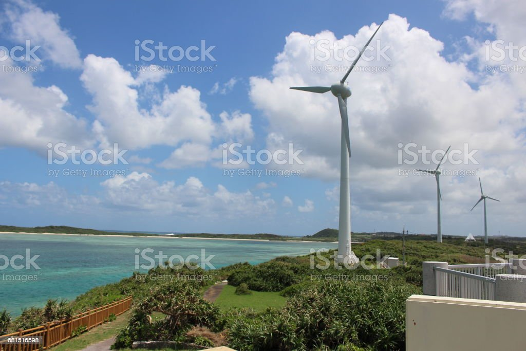 Wind power generators on the beach walkway park in the coral islands in the middle of the ocean. in Miyako island, Okinawa, Japan. stock photo