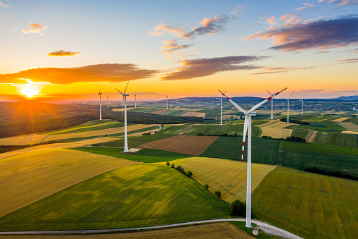 Aerial view of rural patchwork landscape with wind turbines at sunrise