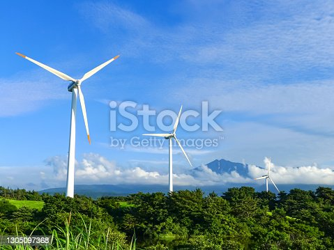 Wind power station on a hill with a mountain view.
