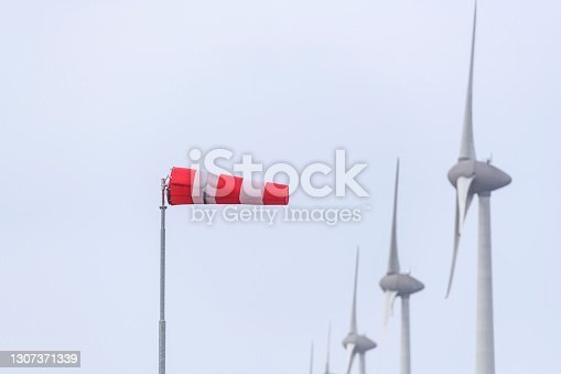 Wind sock in front of wind turbines in a storm at the shore of the IJsselmeer in the Noordoostpolder, Flevoland, The Netherlands.
