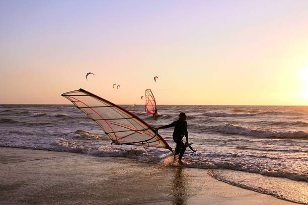 Wind surfer coming out of the surf at dusk stock photo