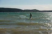 Allmannsdorf, Germany - August 26, 2020: Wind surfer moves the sail of his board out of the water. Brombachsee, Pleinfeld.