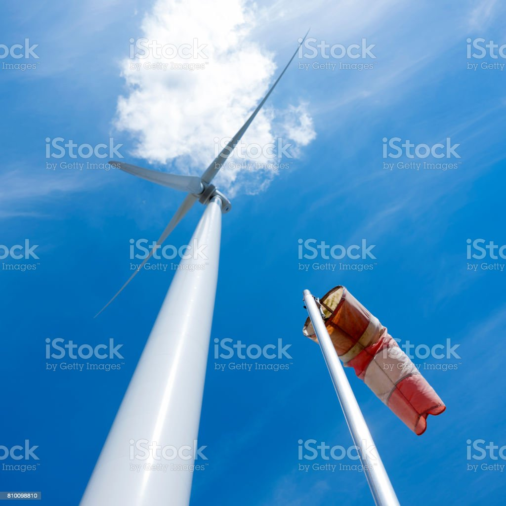 wind turbine and windbag  and white cloudagainst blue sky stock photo