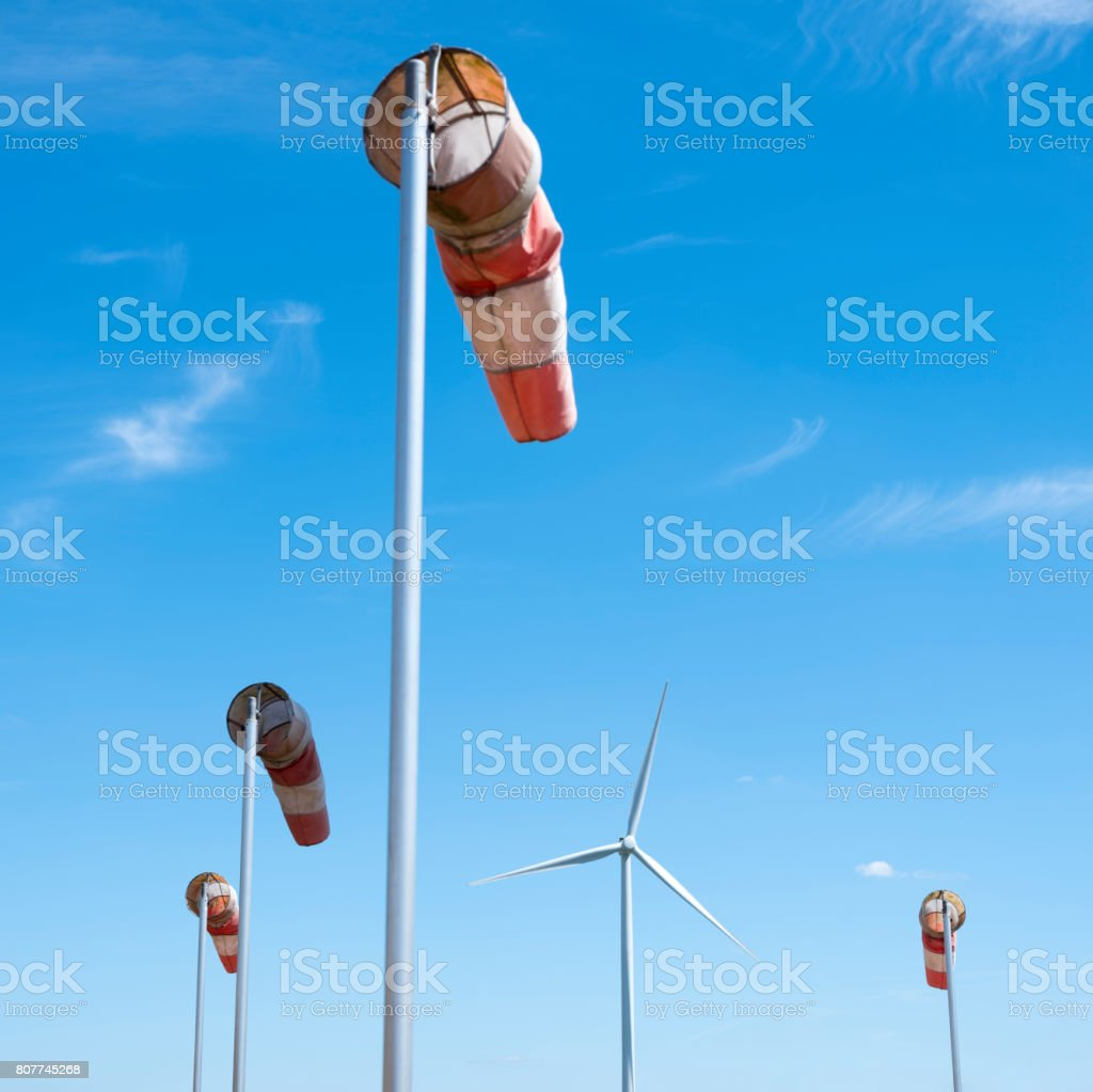 wind turbine and windbag as silhouette against blue sky stock photo